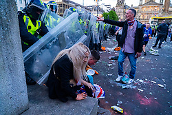 Glasgow, Scotland, UK. 15 May 202. Rangers football supporters  celebrating 55th league victory are cleared from George Square by police in riot gear on Saturday evening. In very violent scenes police were pelted with bottles and items from a nearby construction site as police pushed the supporters into the south west corner of the square. Pic; Woman is pushed by police riot shield.  Iain Masterton/Alamy Live News.