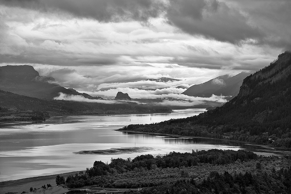"""Columbia River Gorge, Oregon.<br /> Samuel Lancaster, the engineer for the Columbia River Highway, built Vista House on the promontory of Crown Point, some 700 sheer feet above the river.  It was a way station for travelers--""""an observatory from which the view both up and down the Columbia could be viewed in silent communion with the infinite.""""  Sounds dramatic, but the sensation of peering into the prehistoric here is palpable, despite the man-made intrusions.  The Columbia is so big it doesn't even seem to move.  It is the sky that moves, and ominously on this morning;  hopes for sunrise were pretty much dashed until a little break in the overcast transformed the vista for a brief few minutes, to commune with the infinite."""