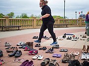 18 MAY 2020 - DES MOINES, IOWA: HEAVEN CHAMBERLIN sets up a memorial of empty shoes in front of the Iowa state capitol in Des Moines. Each Pair Iowa put together a memorial of empty shoes to represent Iowans killed by the COVID-19 pandemic. The memorial is traveling around the state. As of May 18, 355 people in Iowa have died from COVID-19, the disease caused by the Coronavirus (SARS-CoV-2), and 14,955 have tested positive for the Coronavirus.        PHOTO BY JACK KURTZ