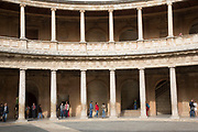 The Alhambra Palace and fortress complex located in Granada, Andalucia, Spain. Tourists inside the Palacia de Carlos V (The Palace of Charles V). Museum of the Alhambra, Museum of Fine Arts.