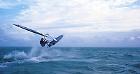 A man jumping on a wind surfer in the gulf of Mexico.