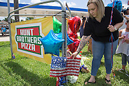 A makeshift memorial grows in front of the B-quick store on Airline in Baton Rouge where officers were killed on Sunday.<br /> Woman  pays respect at the makeshift memorial for fallen officers with a group from Ascension Parish.