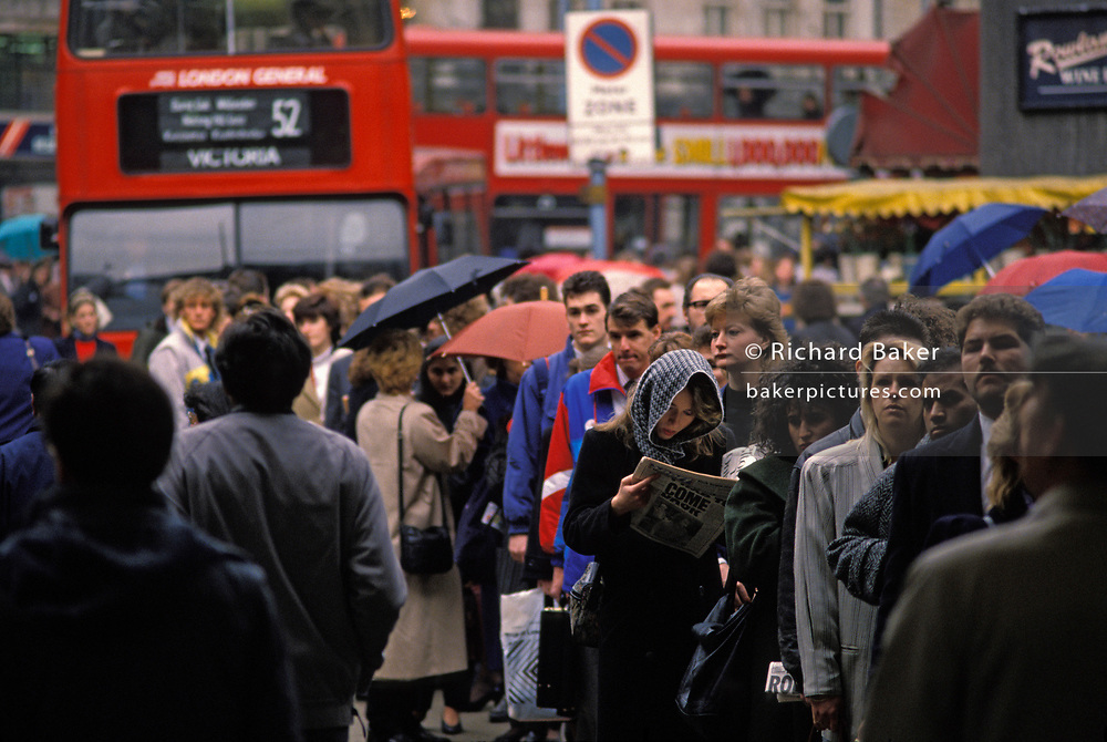 As queues of Londoners line up to gain a ride on a bus during a one-day strike by underground tube unions, a lady with head covered in a scarf reads a newspaper at Victoria Station, on 8th May 1989, in London, England. More than 3,000 British Rail employees launched an unofficial overtime ban, walking out in protest at the end of their eight-hour shifts. Thousands were disrupted at Victoria station in central London, on their way to their inner-city destinations. The buses have a maximum capacity and too few seats for the commuters waiting patiently in line.