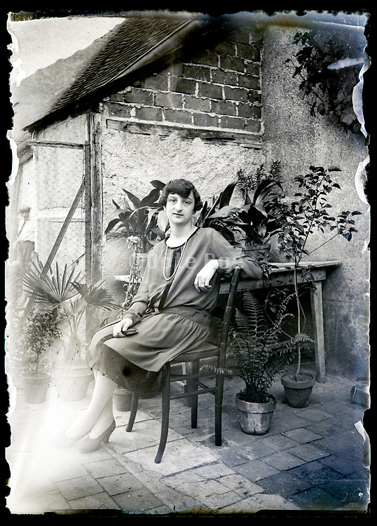 young adult woman sitting in a little courtyard France circa 1920s