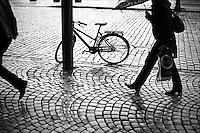 En sykkel står på brosteinen ved en lyktestolpe i Bergen og en dame med paraply spaserer forbi.<br /> Foto: Svein Ove Ekornesvåg