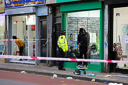 © Licensed to London News Pictures. 30/10/2020. London, UK. A police officer at a crime scene on West Green Road in Tottenham, north London, following the stabbing of a man in his 20s. A medical kit is seen outside a hairdresser. Photo credit: Dinendra Haria/LNP