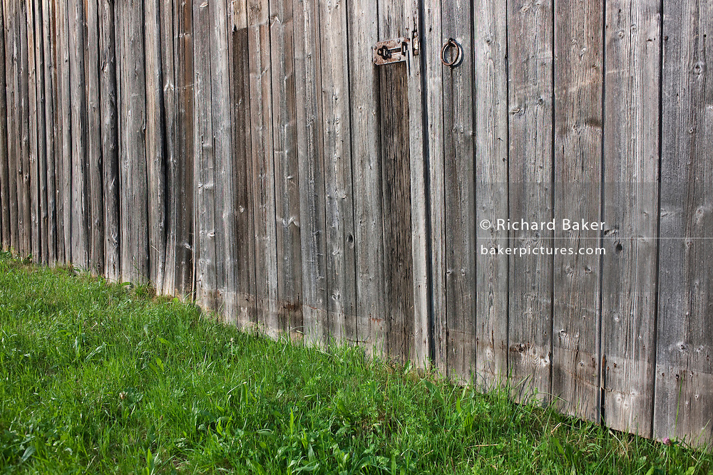 Weather-beaten wooden panels of barn doors in a meadow near village of Kälbermühle in German Black Forest region.