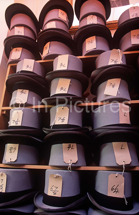 Top hats are stacked along with their head size labels on shelves inside a branch of meanswear rental business Moss Bros, on 14th October 2000, in London, England.