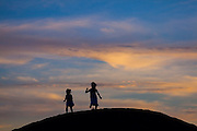 Girls play at sunset on the beach at Waimea, Kauai, Hawaii.