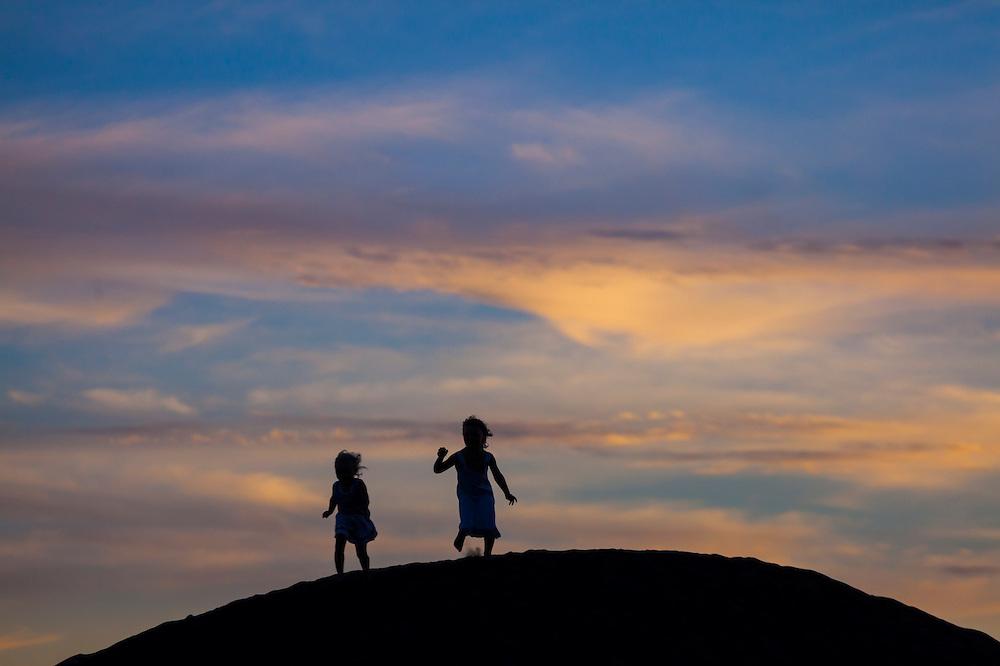 Girls play at sunset on the beach at Waimea, Kauai, Hawaii.