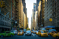 Hustle and bustle as taxis and travelers fill the streets of Manhattan in New York City.