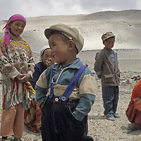 A nomadic Kyrgyz mother and her children relax near near sand dunes in the Pamir Mountains of Xinjiang, China.