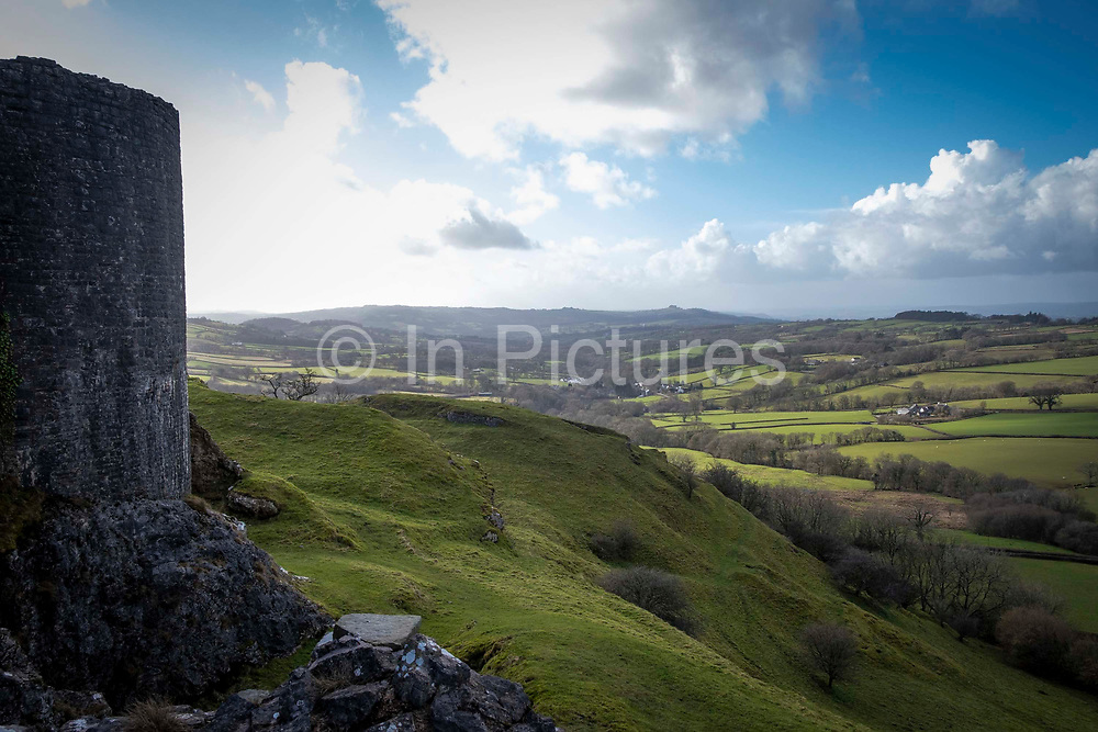 Dramatic landscape views of Carmarthenshire from Carreg Cennen Castle on 18th February 2019 in Trapp, Powys, Wales, United Kingdom.  The castle was built at the top of a limestone cliff, it is dated back to the 13th century, although there is archeological evidence of Roman and prehistoric occupation on the site. The castle has been in a ruinous state since 1462 and is under the care of Cadw, the Welsh Government historic environment service.