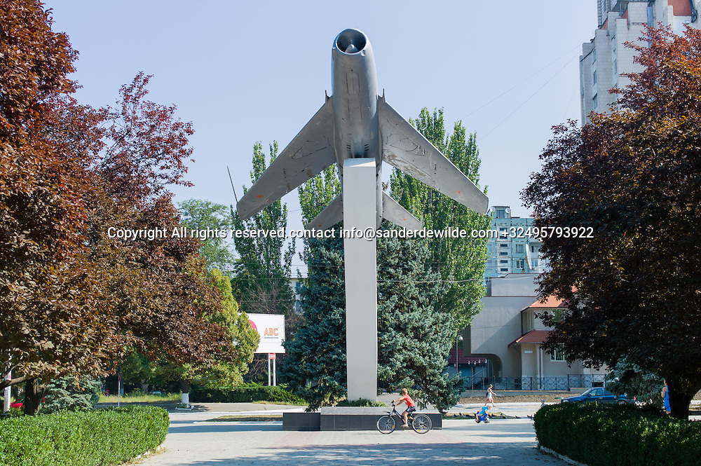 20150829  Moldova, Transnistria,Pridnestrovian Moldavian Republic (PMR) Tiraspol A MIG fighter monument in Tiraspol stands at a square in between appartmentsbuilding. A boy on a bicycle circles around the monument