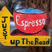 A colorful sign points the way to a cafe for an Espresso coffee break and some warmth in wintertime Chimayo, New Mexico.