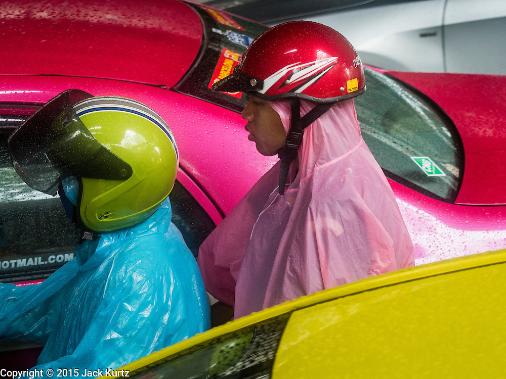 """16 SEPTEMBER 2015 - BANGKOK, THAILAND: Men with ponchos on a motorcycle during a rainstorm in Bangkok. The remnants of tropical storm """"Vamco"""" hit Bangkok Wednesday. The storm, downgraded to a tropical depression, brought bands of rain to central Thailand, including Bangkok. The Thai Meteorological Department said the storm would help alleviate the drought that has gripped Thailand since late last year.     PHOTO BY JACK KURTZ"""