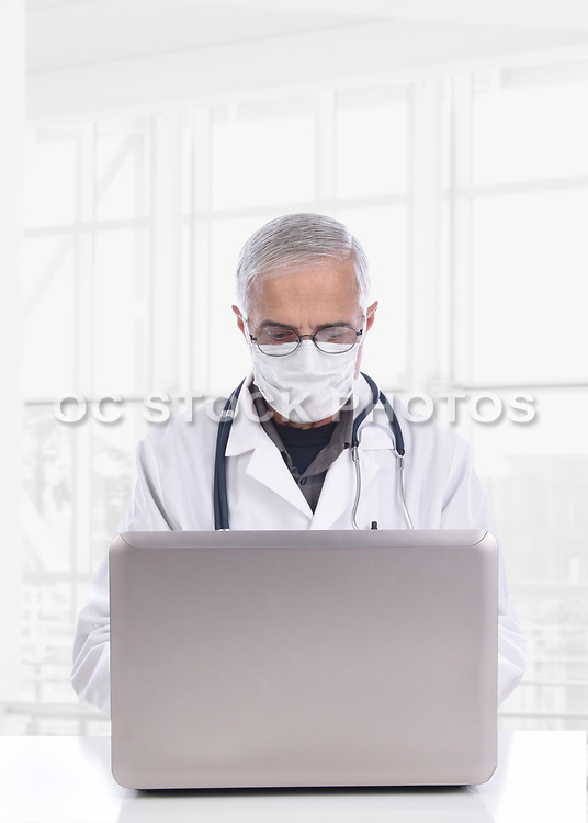 Doctor Wearing a Surgical Mask Sitting at a Desk Using a Computer