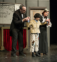 """Mr.  and Mrs. Sowerberyy (Aaron Witham and Patte Sarausky) check over Oliver (Tyler Browne)  during Thursday's dress rehearsal for the Streetcar Company's production of """"Oliver"""" at the Interlakes High School auditorium.  (Karen Bobotas/for the Laconia Daily Sun)"""