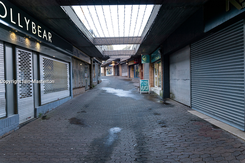 Hamilton, Scotland, UK. 25 November 2020. Hamilton in South Lanarkshire, very quiet during severe level 4 lockdown imposed by the Scottish Government.  Non essential businesses , bars, restaurants and shops are closed. Much of the central regions of Scotland are under the highest level of lockdown.  Pictured; Shopping arcade with all shops closed and shuttered.  Credit.  Iain Masterton