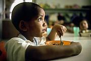 A young boy is fed in a school nursery, Rio de Janeiro, Brazil.