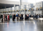 People waiting to check in inside Malaga airport, Spain