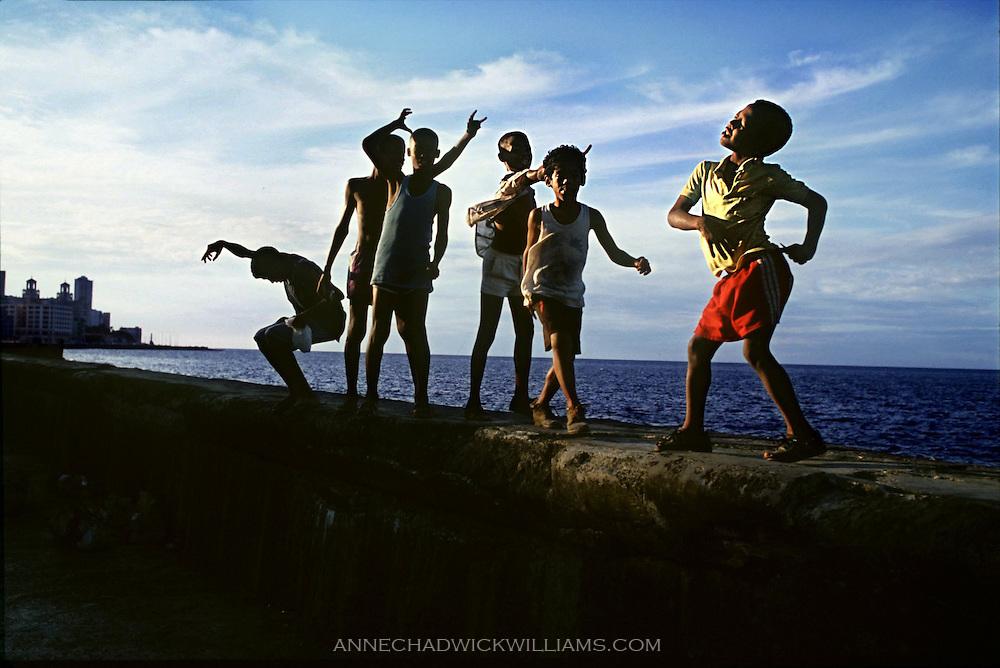 Boys dance along the malecon or sea wall in Havana, Cuba.
