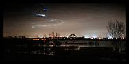 Nederland, Culemborg, 14 jan 2012.Brug bij Culemborg in de nacht, uiterwaarden van de Lek op de voorgrond. Een trein trekt een lichtspoor over de brug .Foto (c): Michiel Wijnbergh..Bridge at Culemborg in the night, floodplains of the river Lek in the foreground.
