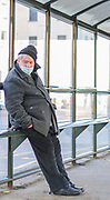 27th February, Cheltenham, England. A portrait of a man at a bus stop wearing a mask during the third national lockdown.