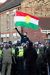 © under license to London News Pictures. 11/12/2010. Continuing their protests in towns and cities across the UK, the English Defence League protest against militant Islam in Peterborough. This man is waving the Kurdistani flag, as police lead Muslim counter protester to the local mosque