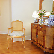 A very ornate European looking wooden chair with caned back and a checked pad on the seat, near a wall and to the right of a large French  cupord with a large mirror and oriental lamp and vase on its marble counter. The floors are wood and there is a hallway behind the wall and chair.
