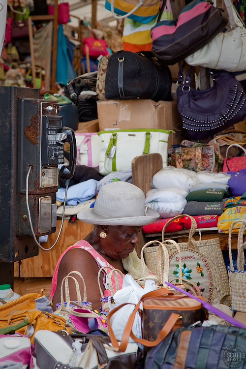 Old woman sitting by an old phone in a souvenir shop. Prince George Wharf, Nassau, Bahamas.