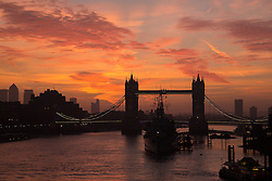 © Licensed to London News Pictures. 18/10/2013. London, UK. A pink and orange sunrise is seen behind Tower Bridge on the River Thames in London on 18 October 2013. Photo credit : Vickie Flores/LNP