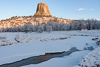 The Belle Fourche River flows beneath Devils Tower after a fresh snowfall.