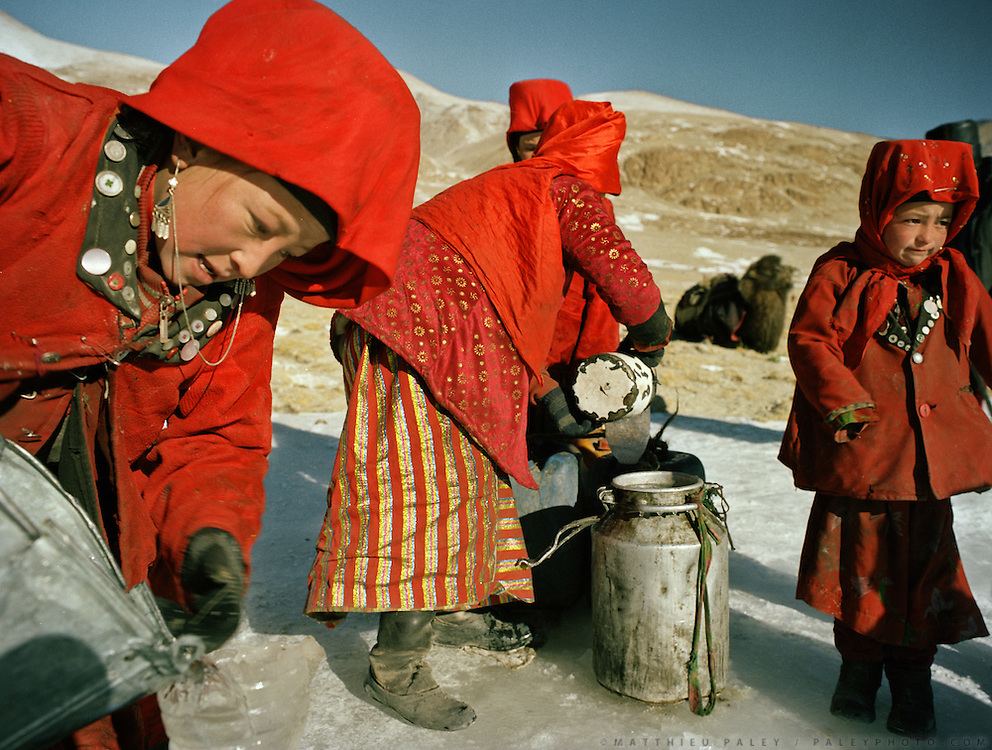 Tella Bu (left)..Every morning, the girls from the Khan's camp are in charge of getting water all throughout winter in sub zero temperature. They have to dig hole in the ice to hope and find the spring that always freezes overnight..Qyzyl Qorum campment, Abdul Rashid Khan's camp (leader of the Afghan Kyrgyz). .Winter expedition through the Wakhan Corridor and into the Afghan Pamir mountains, to document the life of the Afghan Kyrgyz tribe. January/February 2008. Afghanistan