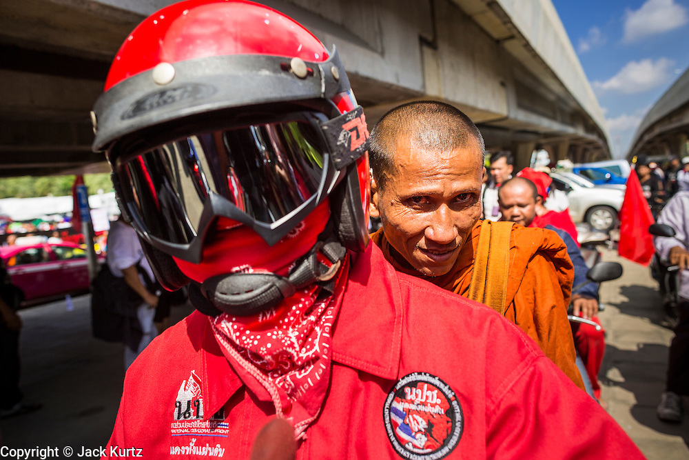 08 MAY 2013 - BANGKOK, THAILAND:   A Buddhist monk rides with a Red Shirt in a Red Shirt motorcade to the Thai Parliament. A splinter group of the Red Shirts, Thai supporters of exiled Prime Minister Thaksin Shinawatra, have besieged the Thai Constitutional Court for the last three weeks calling for the resignation of the justices, who have indicated they might oppose a proposed constitutional reform which would grant amnesty to people convicted of political crimes since 2007. This would probably include Thaksin. The justices have refused to step down. Wednesday the protesters moved their protest to the Thai Parliament, which is largely powerless to intervene. PHOTO BY JACK KURTZ