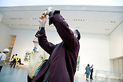 tourist taking an image of a large sculpture in  the Museum of Modern Art New York