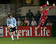 New England Revolution goalkeeper Doug Warren upends Chicago Fire forward Calen Carr during the first half of the U.S. Open Cup quarterfinals, at Toyota Park in Bridgeview, Ill., Wednesday, August 23, 2006.
