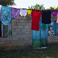 Central America, Cuba, Caibarien. Clothesline in front of home with painted doors and windows.