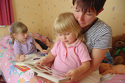 Mother reading with daughter in bedroom; older sister lying on bed with colouring book,