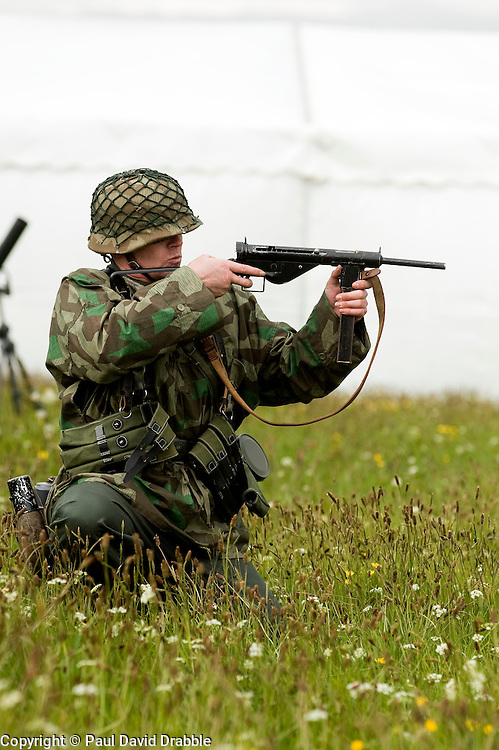 Member of the Northern World War Two Association. Portraying a soldier from 21st Panzer Division returns fire using his MP40 during a large scale Western Front  battle reenactment. .Scarborough.Sunday 30th May 2010 .Images © Paul David Drabble.