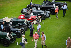 © Licensed to London News Pictures. 13/07/2015. Epsom, UK. Classic car enthusiasts examine cars on show before the race. The start of The Royal Automobile Club 1000 Mile Trial 2015 at Woodcote Park in Epsom, Surrey. The event, which starts and finishes at Woodcote Park, takes a fleet of over 40 classic cars from around the world, through a 1000 mile trial around the UK.  Photo credit: Ben Cawthra/LNP
