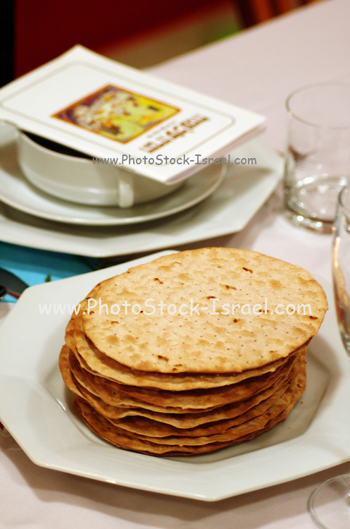 """Matza and Haggada for pesach on the table set for a Jewish Festive meal on Passover (transliterated as Pesach or Pesah), also called chag HaMatzot - Festival of Matzot is a Jewish holiday beginning on the 15th day of Nisan, which falls in the early spring and commemorates the Exodus and freedom of the Israelites from ancient Egypt. Passover marks the """"birth"""" of the Jewish nation, as the Jews were freed from being slaves of Pharaoh and allowed to become servants of God instead."""