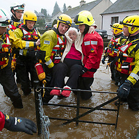 Flooding in the village of Comrie, Perthshire after heavy rain caused the River Ruchil to burst it's banks and flood the surrounding streets.....  Firefighter's rescue and elderly resident from her house on Glebe Road as the floodwater rises. <br /> Picture by Graeme Hart.<br /> Copyright Perthshire Picture Agency