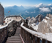 """From the ski resort of Cortina d'Ampezzo, ride a cable car lift to the sun deck at Tofana di Mezzo (3244 meters / 10,643 feet, third highest peak in the Dolomites) in Tofane mountain group, in the Dolomiti (a part of the Southern Limestone Alps), in the Province of Belluno, Veneto region, Italy, Europe. This ski resort hosted the 1956 Winter Olympics and motion pictures including: """"The Pink Panther"""" (1963), """"For Your Eyes Only"""" (1981, James Bond stunt sequences); and """"Cliffhanger"""" (1993). Here at the head of Valle del Boite, nearby peaks include Pomagagnon to the north, Cristallo to the northeast, Faloria and Sorapiss to the east, and Becco di Mezzodì, Croda da Lago and Cinque Torri to south. The Dolomites were declared a natural World Heritage Site (2009) by UNESCO. Panorama stitched from 5 overlapping photos."""