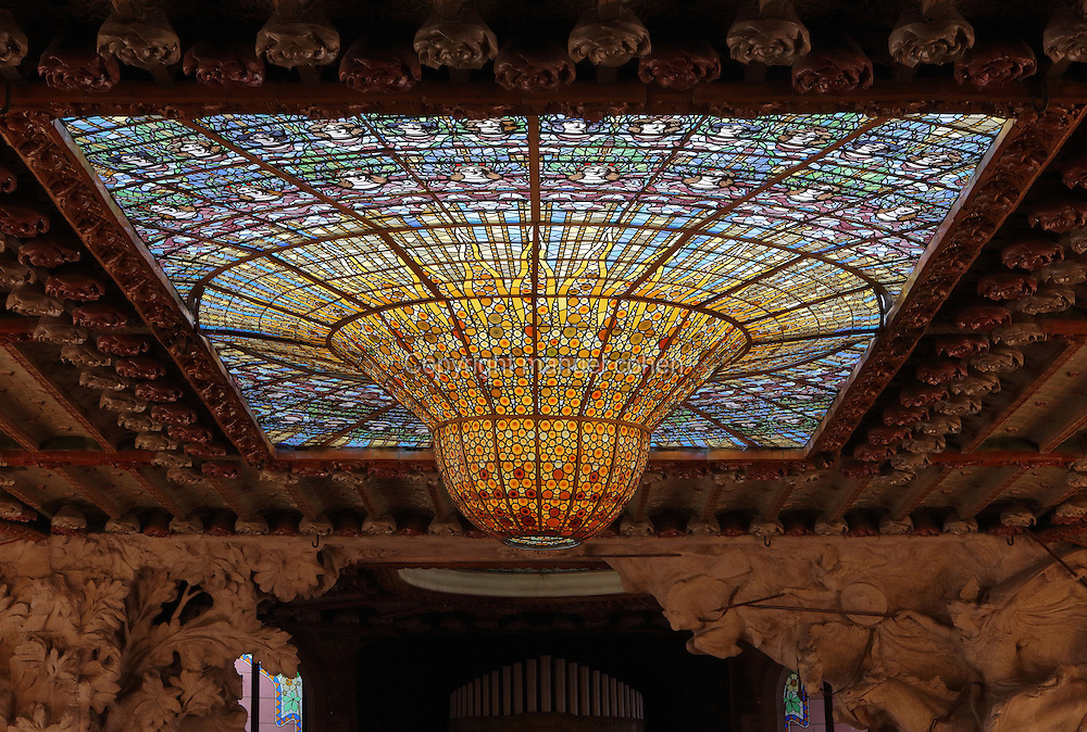 Huge stained glass drip-shaped skylight by Rigalt Granell & Cia, which illuminates the Concert Hall at the Palau de la Musica Catalana, built 1905-8 and designed by the Catalan Modernist architect Lluis Domenech i Montaner, 1850-1923, in Casc Antic, Barcelona, Catalonia, Spain. The skylight resembles an orange sun in a blue sky, surrounded by a choir of young women. The stained glass windows and skylight mean that no artificial lighting is needed in the Concert Hall during the day. The hall was built for the Orfeo Catala choral society in Catalan Modernist style, with art nouveau inspired organic forms and much attention to decorative detail. The concert hall was listed in 1997 as a UNESCO World Heritage Site. Picture by Manuel Cohen