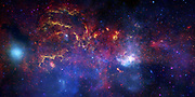 NASA's Great Observatories Examine the Galactic Center Region. November 10, 2009: A never-before-seen view of the turbulent heart of our Milky Way galaxy. The composite image features the spectacle of stellar evolution: from vibrant regions of star birth, to young hot stars, to old cool stars, to seething remnants of stellar death called black holes. This activity occurs against a fiery backdrop in the crowded, hostile environment of the galaxy's core, the center of which is dominated by a supermassive black hole nearly four million times more massive than our Sun. Permeating the region is a diffuse blue haze of X-ray light from gas that has been heated to millions of degrees by outflows from the supermassive black hole as well as by winds from massive stars and by stellar explosions. cocoons.