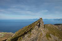 Female hiker descends steep ridge on route to Matmora mountain peak, Austvågøy, Lofoten Islands, Norway