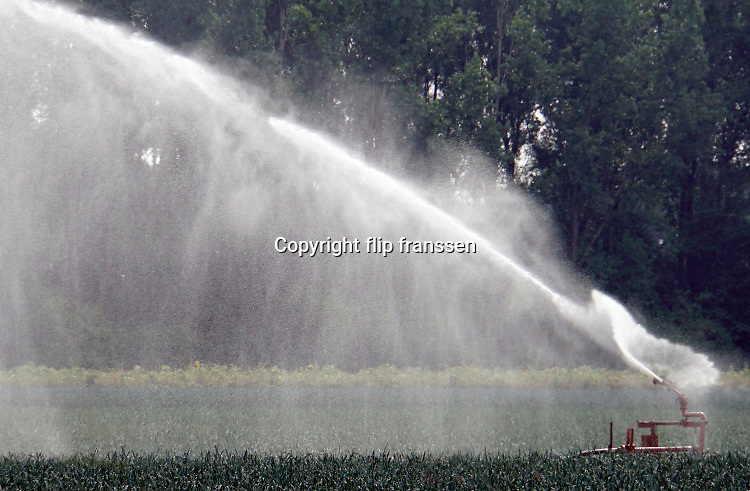 Nederland, Groesbeek, 19-5-2020 Een boer beregent zijn akker nat dmv een waterkanon. Het water wordt uit een put in de grond opgepompt en is dus grondwater. Waterdruppels in waterscherm . Foto: Flip Franssen