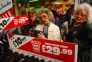 The women ponder the construction and value of ladies shoes that are on sale at a branch of Clarks shoes, in central London. The two females look the same facially and may be sisters, with similar glasses and hairstyles. Shopping together in the city where the busy atmosphere of shopaholics and busy consumers, this scene is frenzied and greedy retail spending and consumerism. The lady on the left has her tongue in her cheek and inspects the sole of a right shoe and its price on the heel. The manufacturer is Ecco, the small town Danish brand that is now available globally.