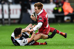Rhys Patchell of Scarlets is tackled by Luke Morgan of Ospreys<br /> <br /> Photographer Craig Thomas/Replay Images<br /> <br /> Guinness PRO14 Round 11 - Ospreys v Scarlets - Saturday 22nd December 2018 - Liberty Stadium - Swansea<br /> <br /> World Copyright © Replay Images . All rights reserved. info@replayimages.co.uk - http://replayimages.co.uk